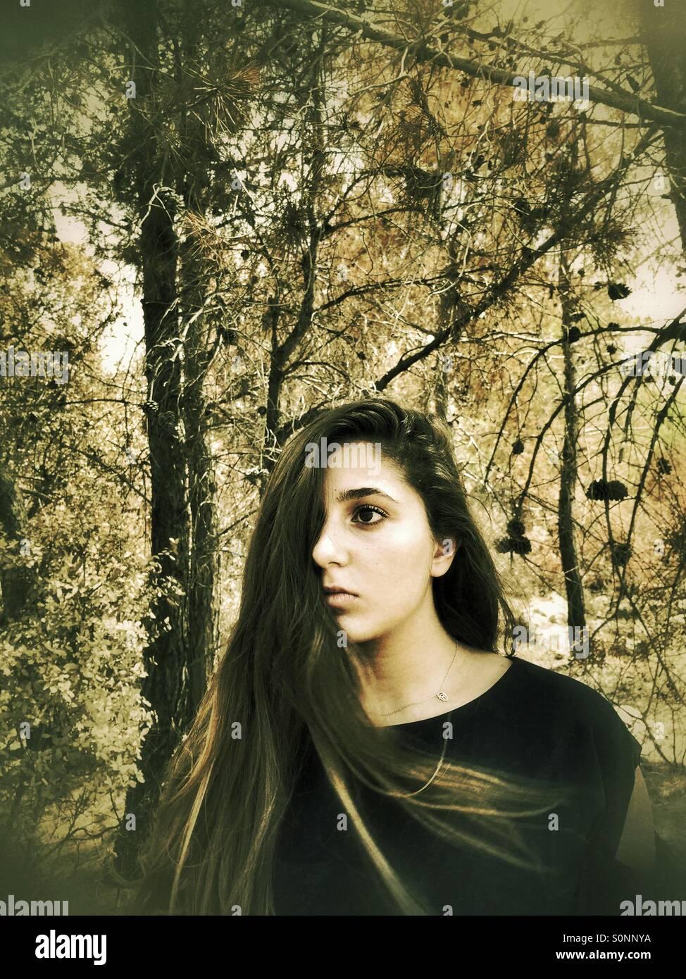 Asustada adolescente mirar lejos en el bosque Foto de stock