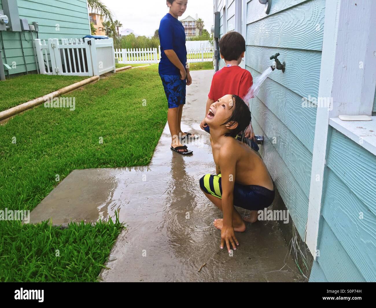 Los muchachos aclarándolo después de nadar. Jugando en el agua. Foto de stock