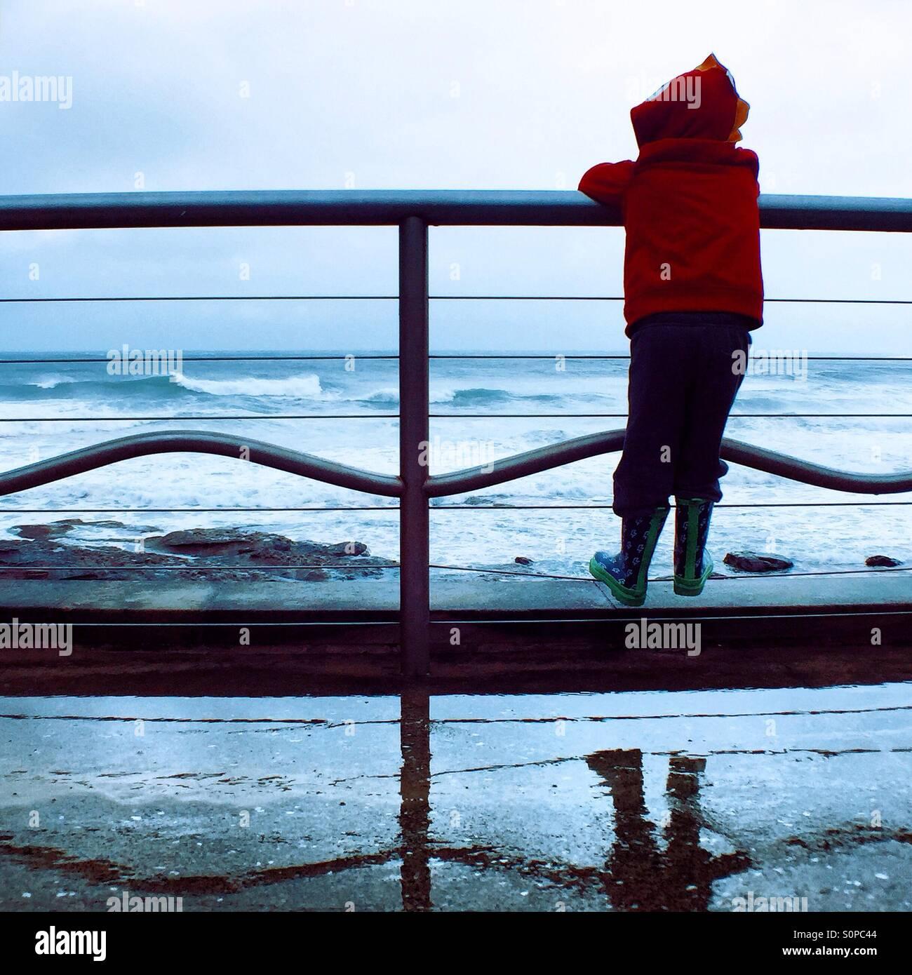 Chico mirando al océano. Imagen De Stock