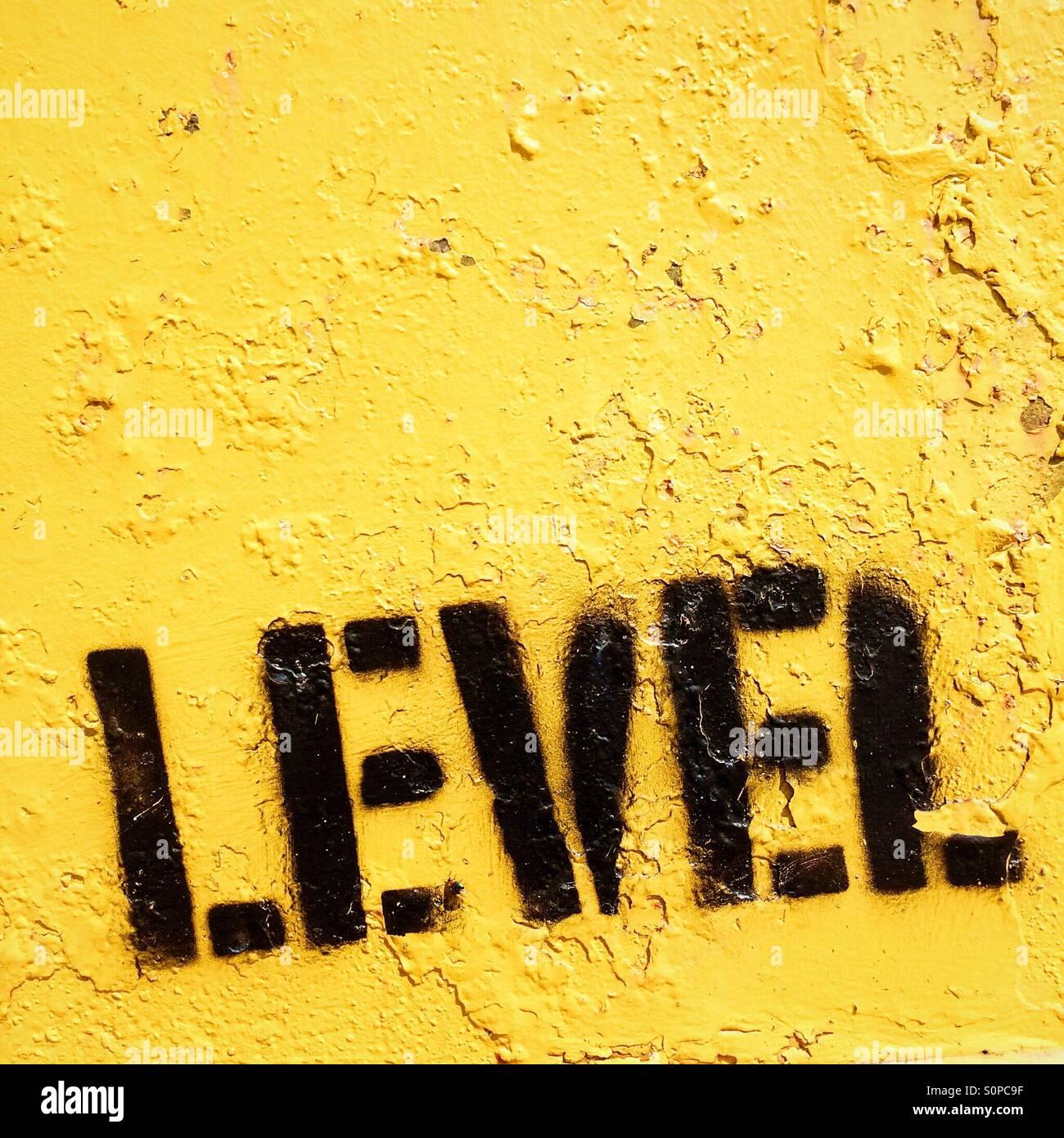 Nivel estampadas en la pintura negra sobre fondo amarillo Foto de stock