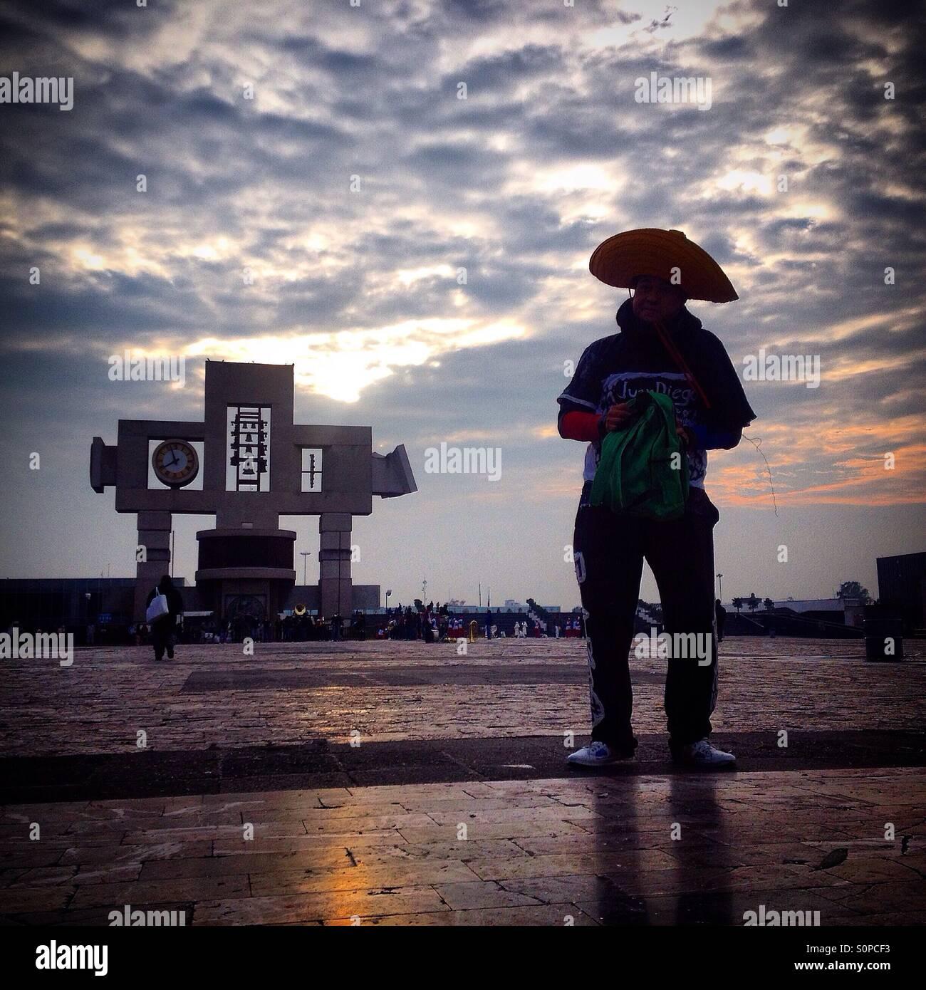 La silueta de un hombre vestido con un Sombrero Mexicano se sitúa delante  de la cruz a735f14a673