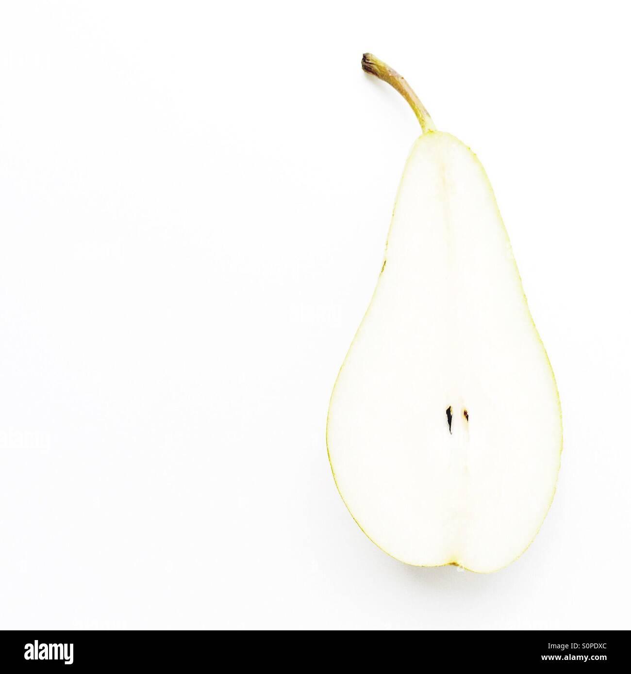 Imagen minimalista de una pera cortada a la mitad Foto de stock