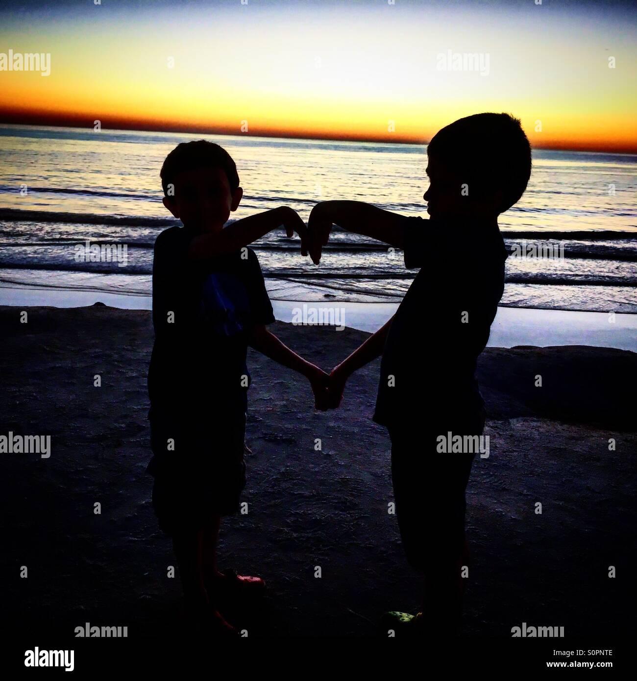 Dos chicos haciendo una forma de corazón durante la puesta de sol en la playa. Imagen De Stock
