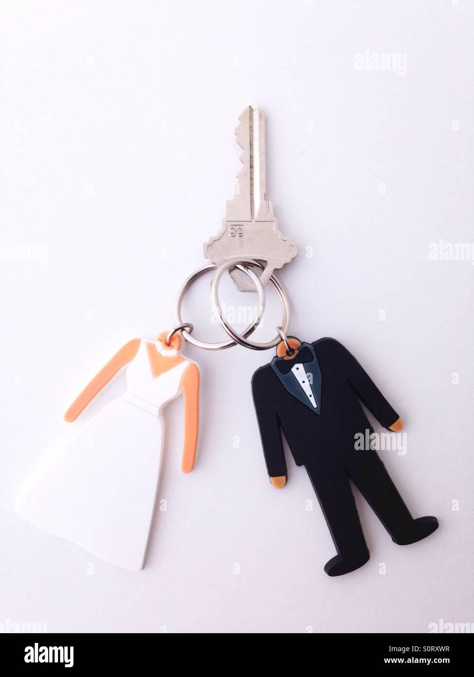 Dos llaveros en forma de la novia y el novio se unieron con una clave. Imagen De Stock