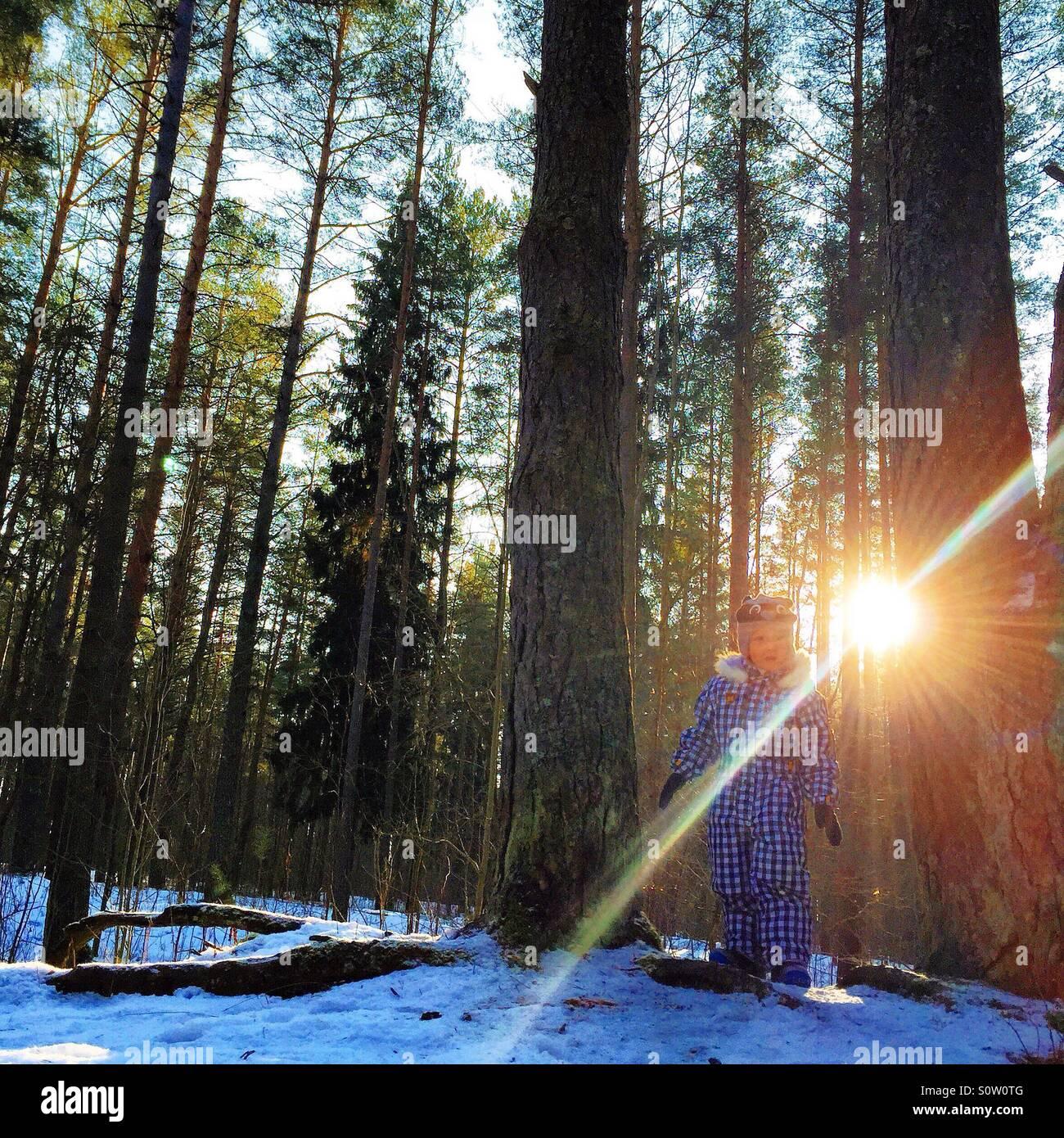 Niño jugando en el bosque en invierno Imagen De Stock