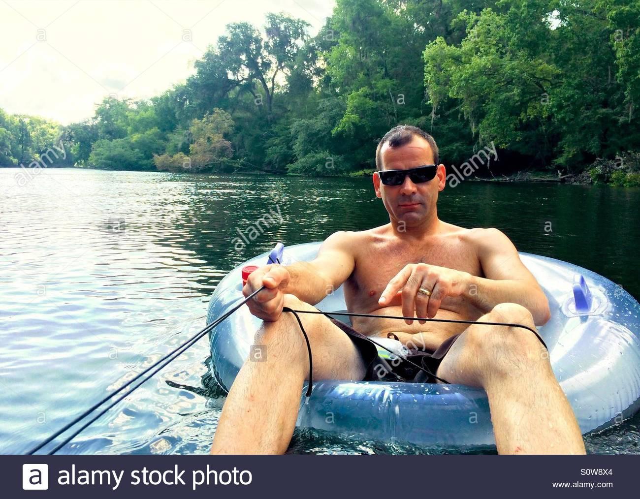 El hombre flotando por el Río Santa Fe en un tubo interior Imagen De Stock