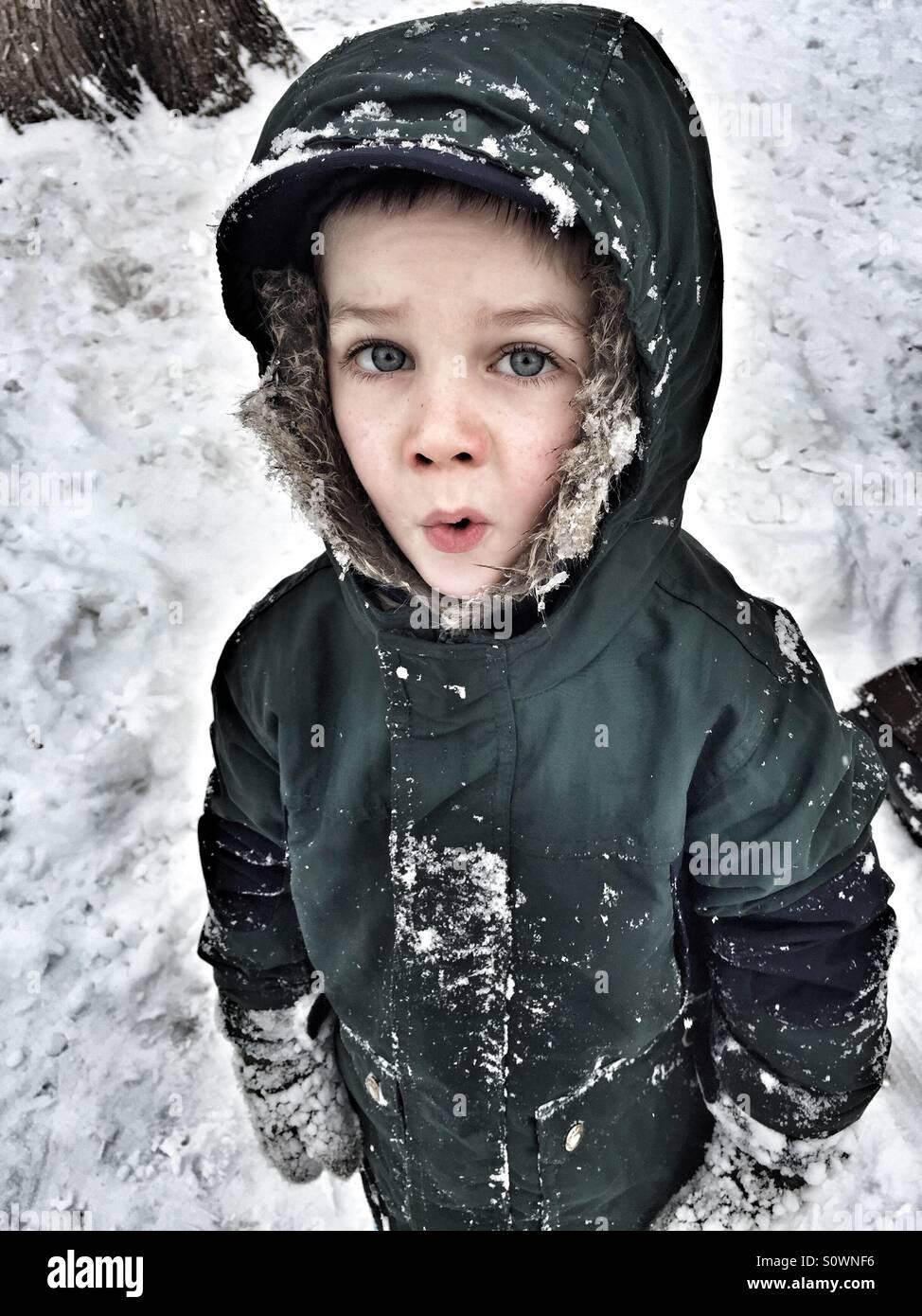 Un muchacho joven con una parka fuera en la nieve en invierno Imagen De Stock