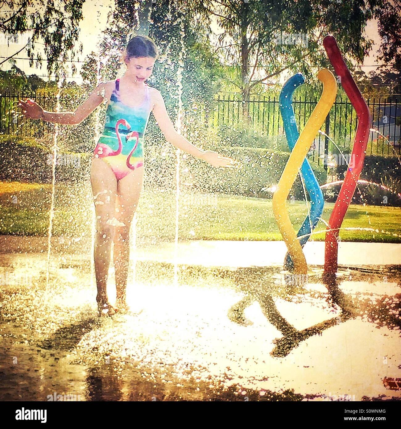Chica en bañador jugando en la fuente de agua potable en verano Imagen De Stock