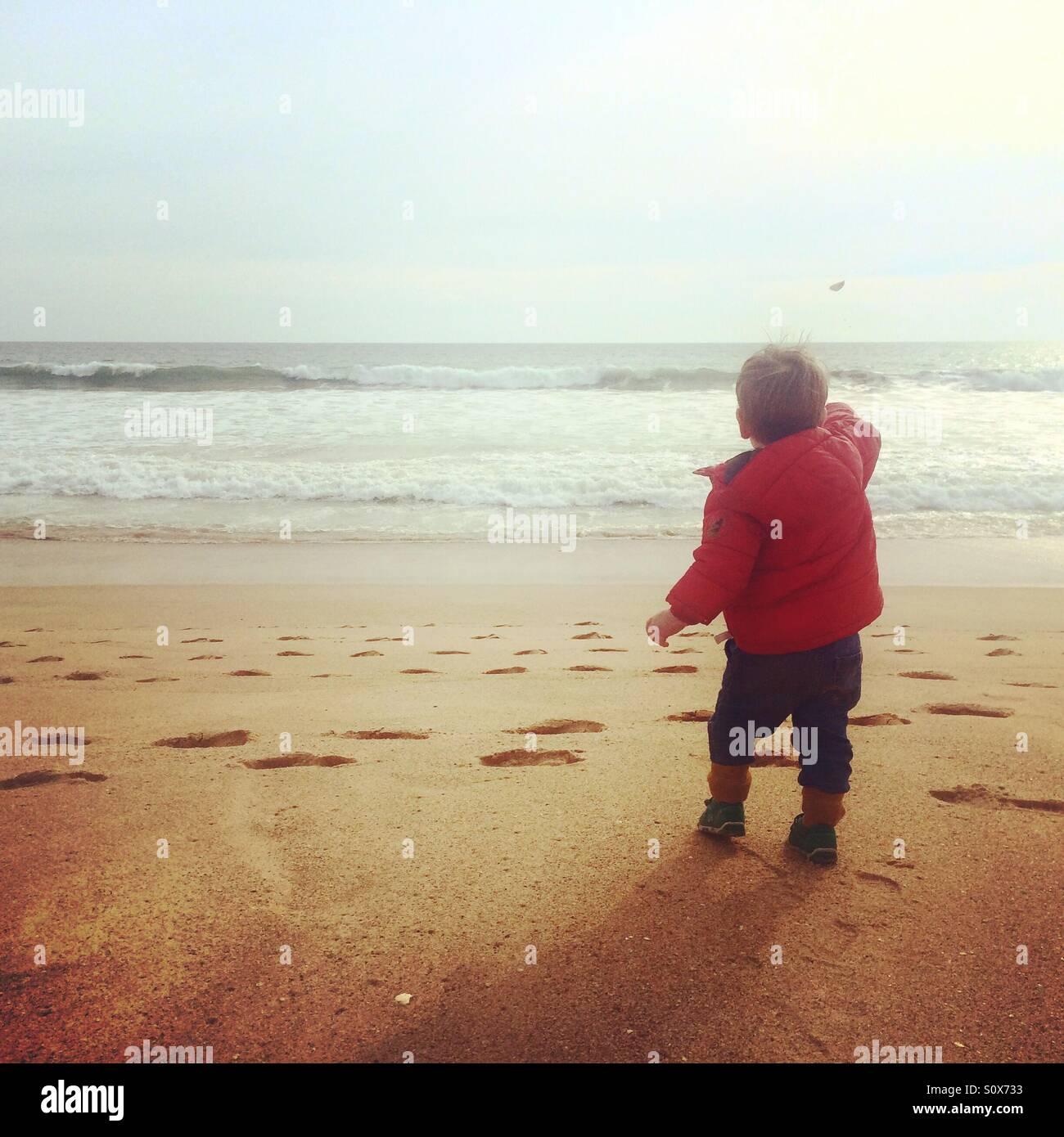 Niño arrojando piedras en el mar en Portugal, Algarve Imagen De Stock