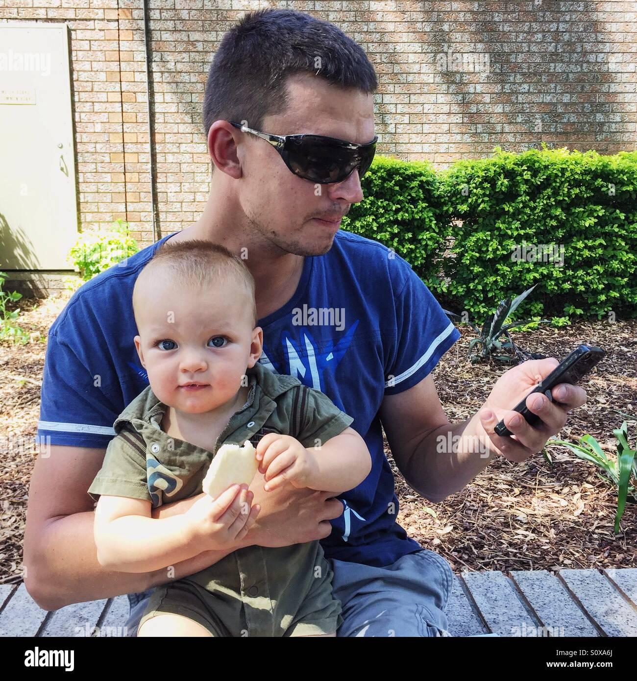 Padre tenga el bebé y mirando al teléfono móvil Imagen De Stock