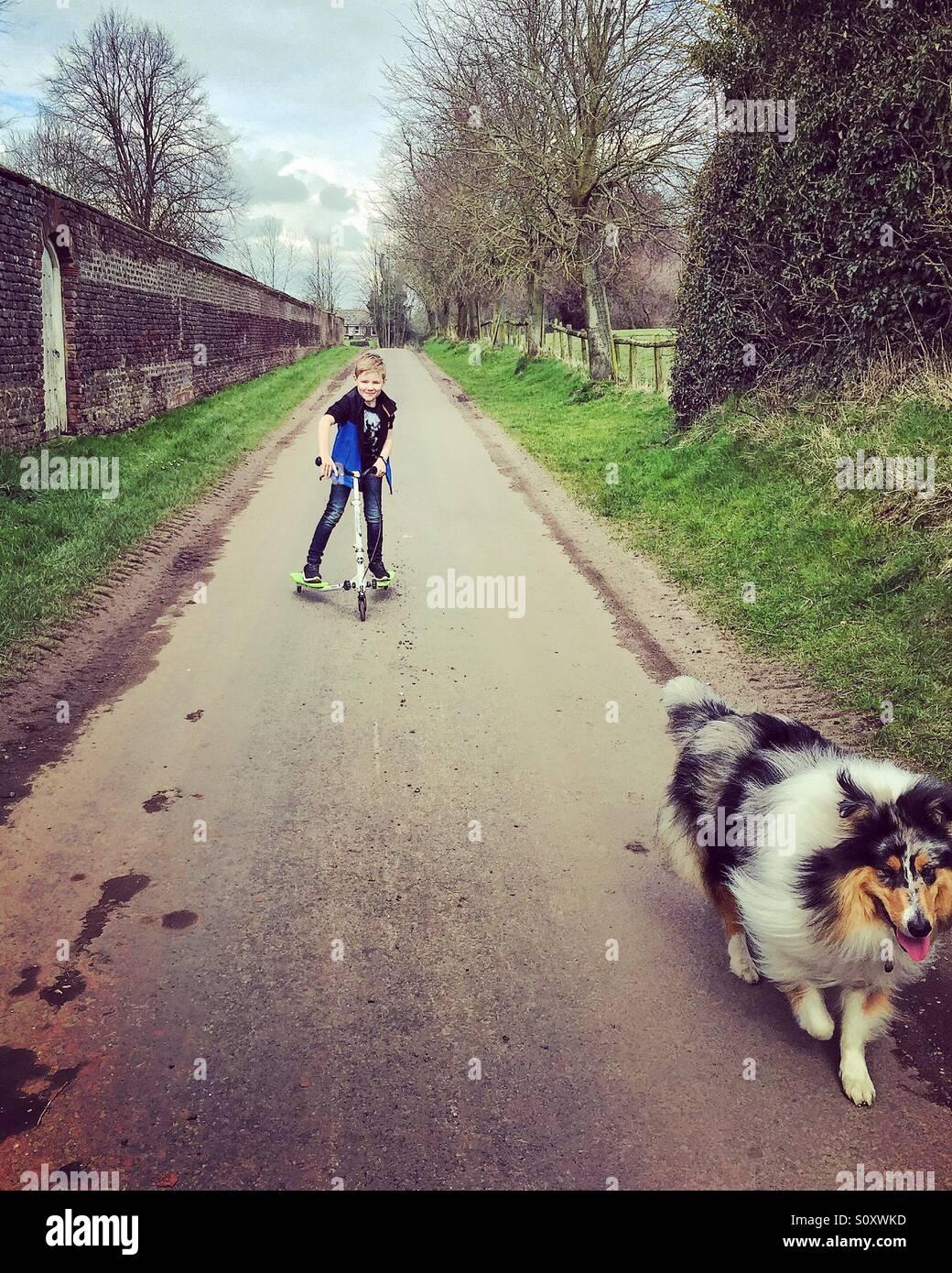 Un muchacho en su scooter tras su perro abajo de un carril del país Foto de stock