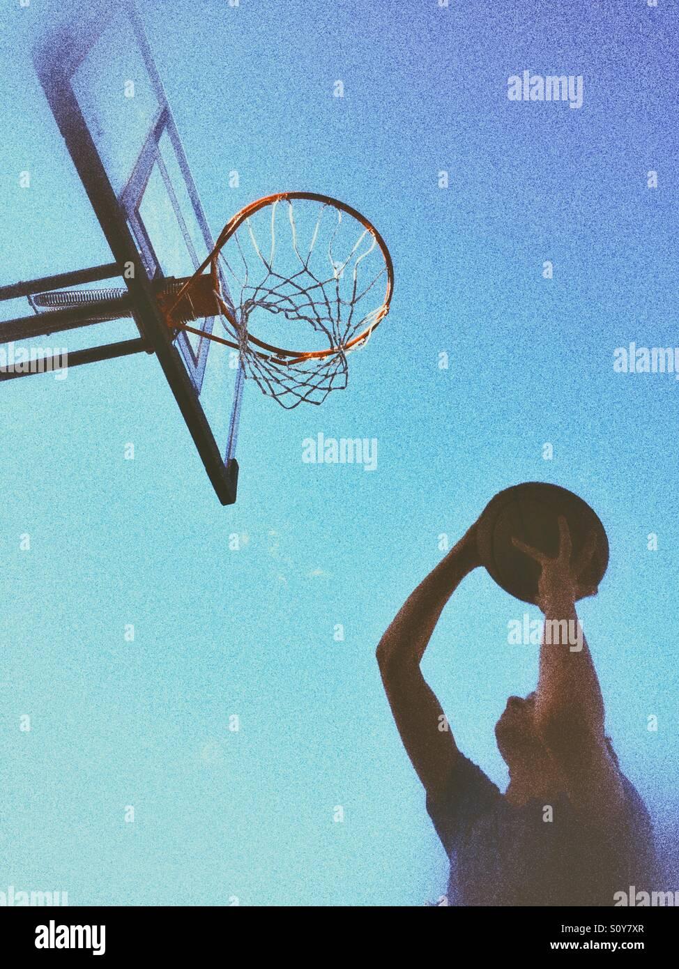 Adolescente disparar una pelota de baloncesto. Disparó al aire libre, luz natural, granulosas editar. Imagen De Stock