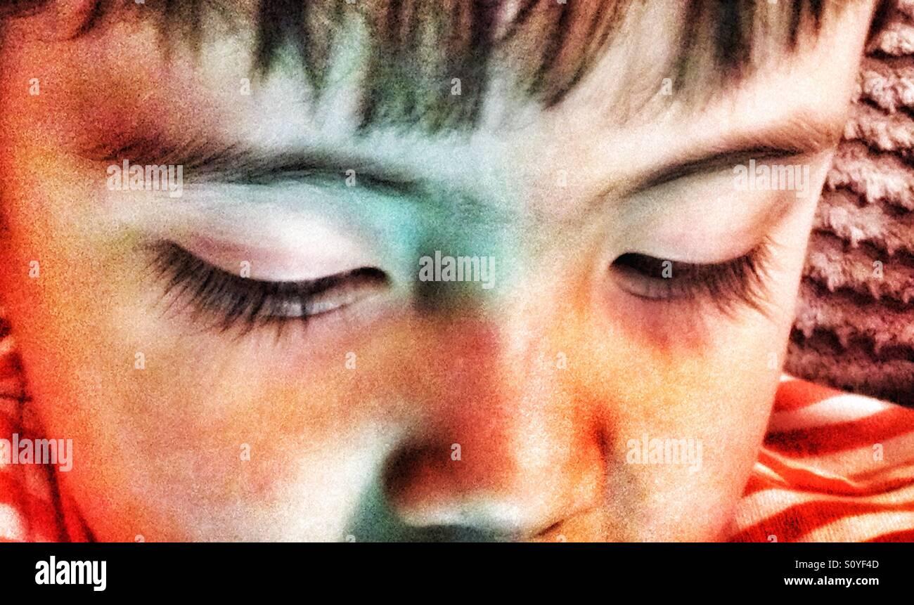 Primer plano de los ojos de un joven como él juega en un equipo tablet pc. Imagen De Stock