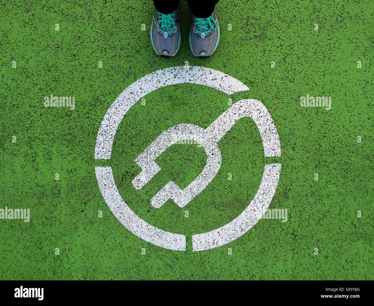 De pie junto a la señal de punto de recarga de coches eléctricos Imagen De Stock