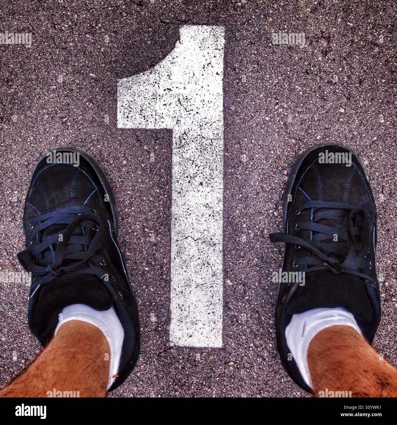 El hombre los pies cerca del número 1 en un parking. Imagen De Stock
