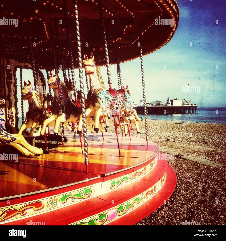 Carrusel de estilo antiguo con la playa de Brighton Pier en segundo plano. Imagen De Stock