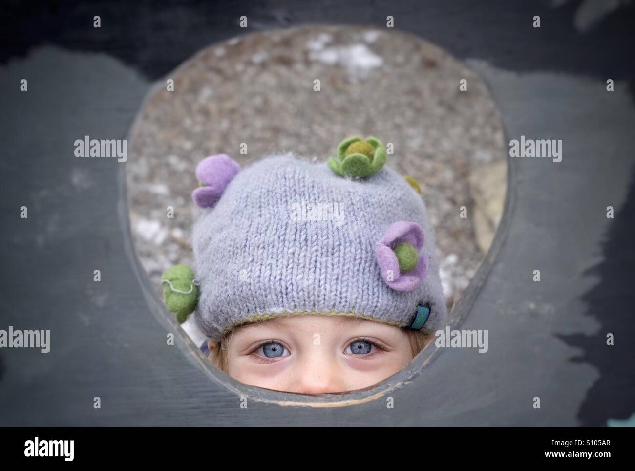 Una chica joven peeking a través de un orificio. Imagen De Stock