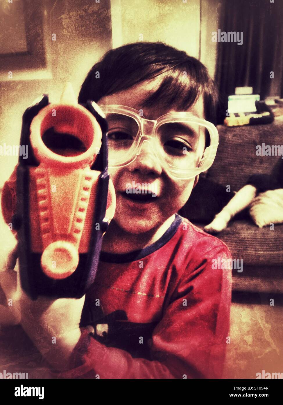 Un chico gafas protectoras, jugando con una pistola de juguete. Imagen De Stock