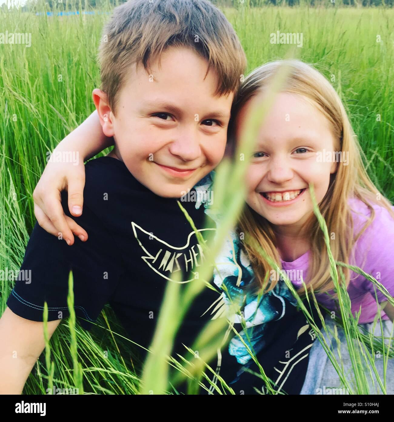 Feliz hermanos abrazarse mutuamente y sonriente, sentado afuera en un alto sobre una fina hierba verde, Hermoso, Imagen De Stock