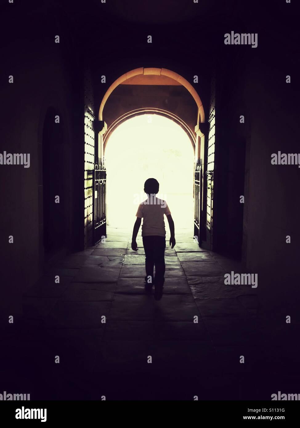 Muchacho caminando hacia la puerta abierta Imagen De Stock