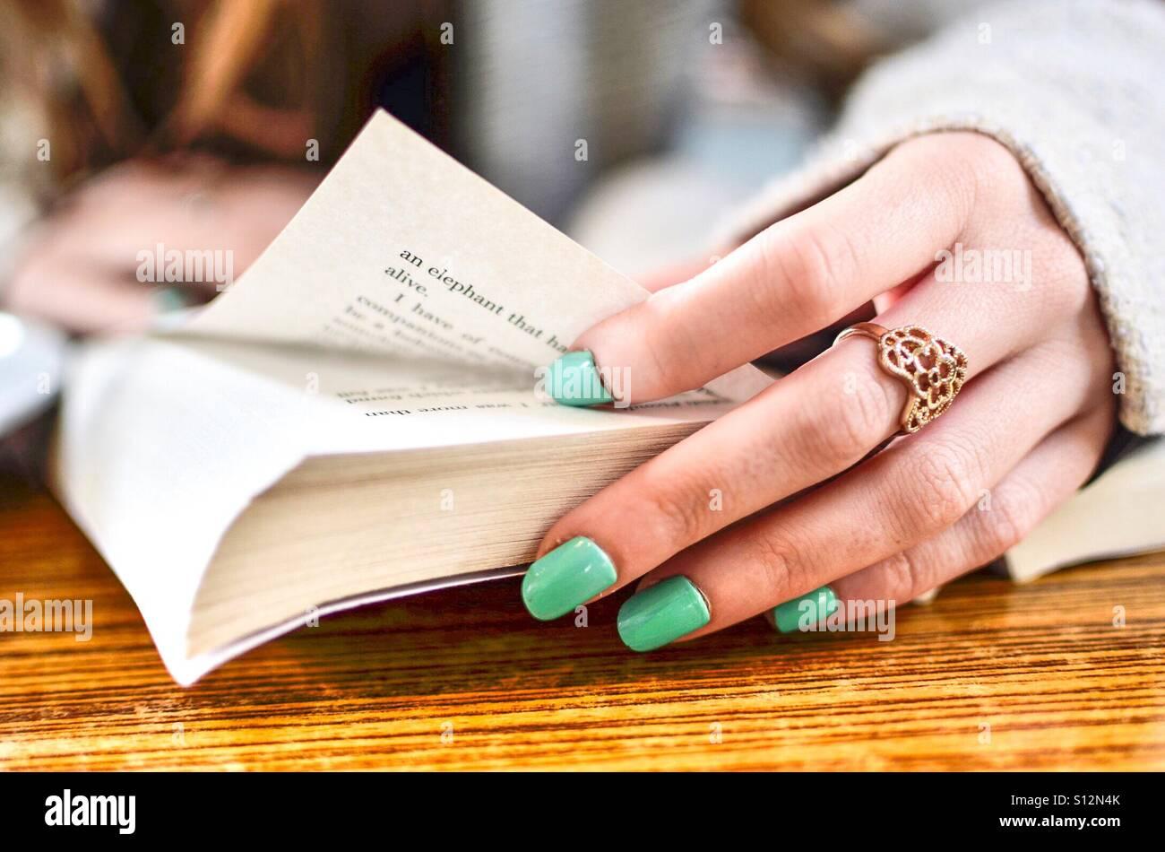 Las mujeres leyendo un libro con las uñas de color turquesa y bonito ...