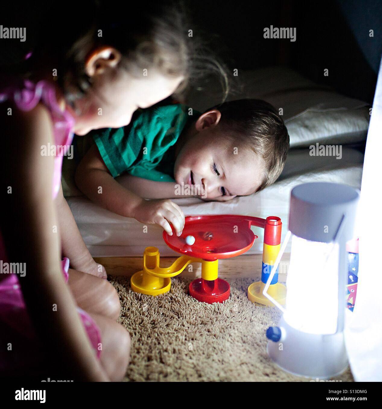Niño y su niña juegan con un juguete run de mármol a la hora de acostarse por lámpara de luz Imagen De Stock