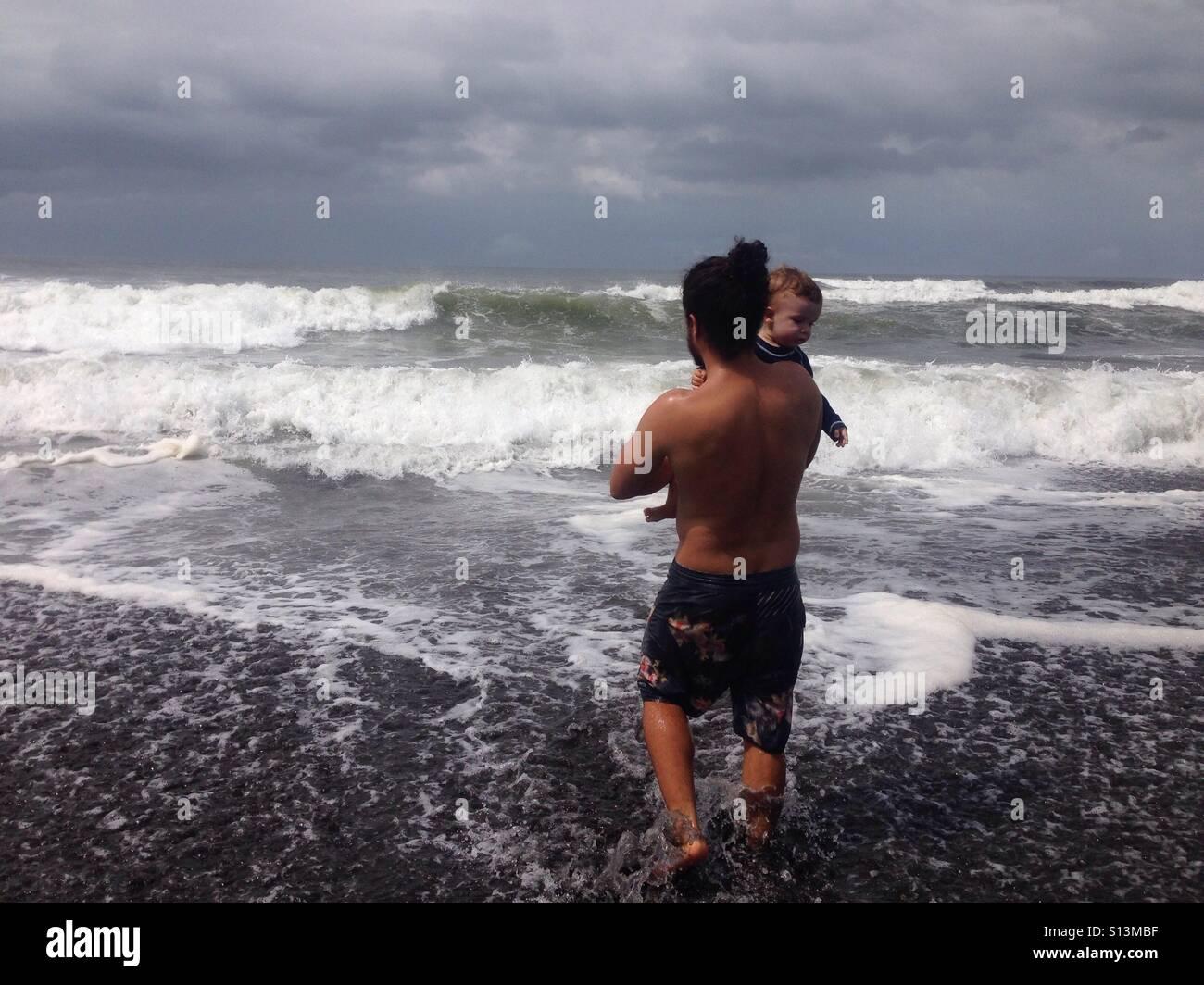 Amor paternal, el padre con el bebé disfruta de las olas en el mar pacífico ONU Guatemala Imagen De Stock