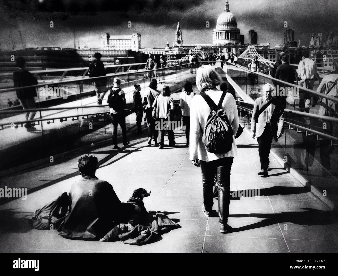 Cuestiones sociales documental fotografía de un hombre y un perro sentado viendo los viajeros y turistas que Imagen De Stock