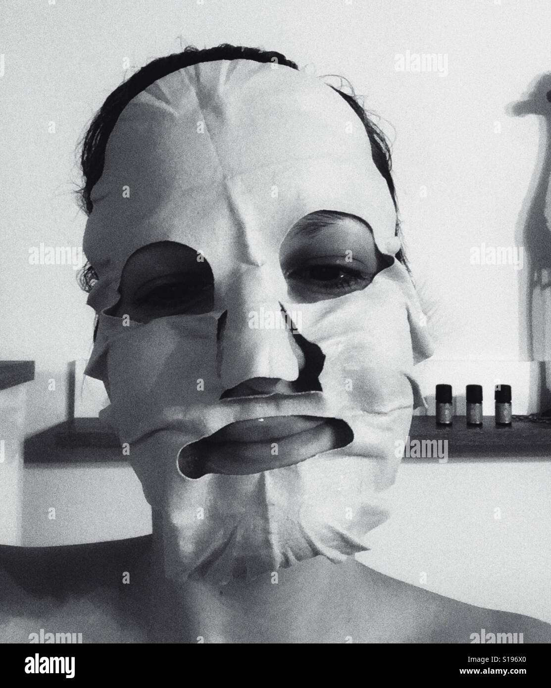 Cara con máscara de belleza en blanco y negro y la silueta de la jirafa detrás Foto de stock