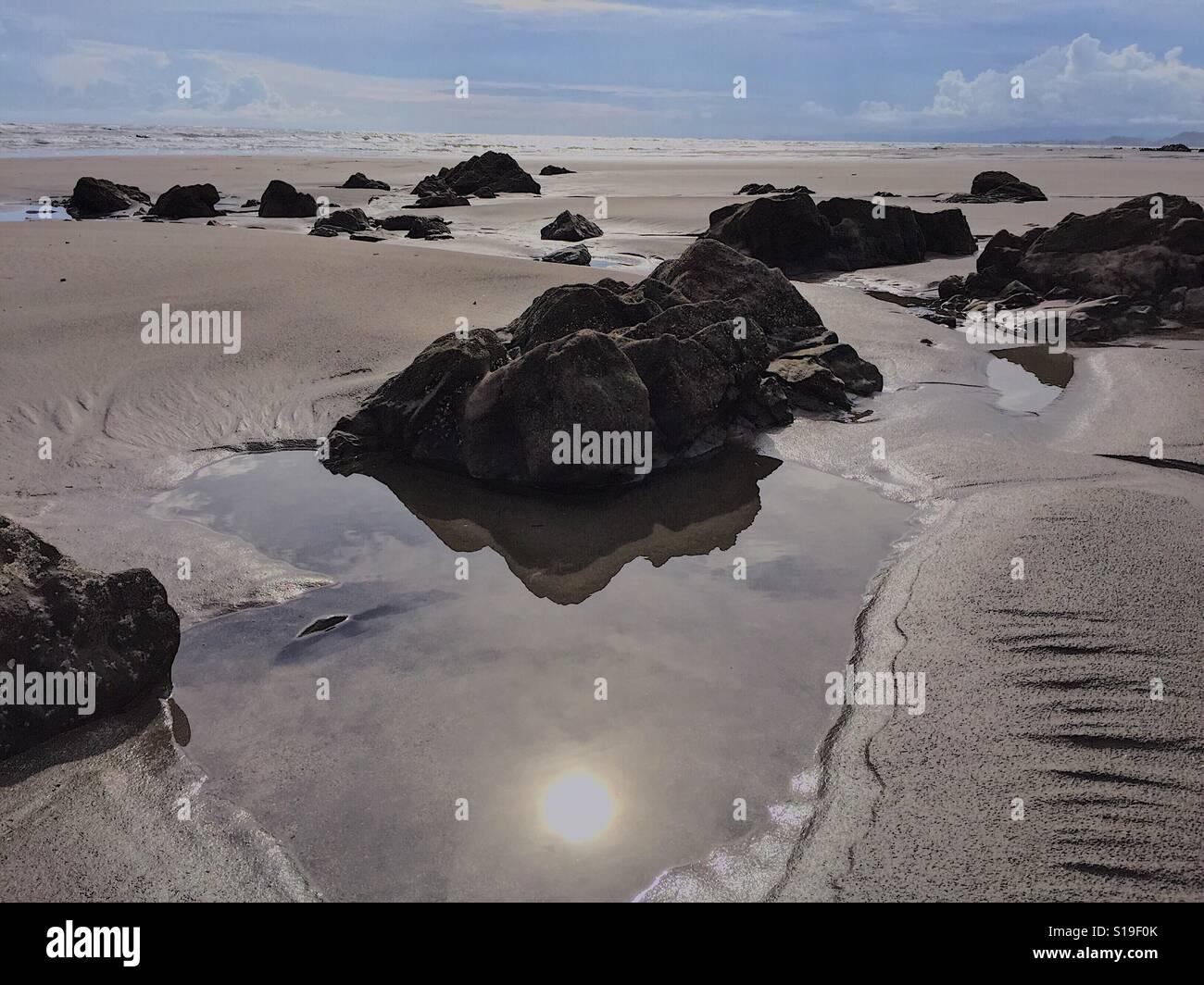 Reflejo del sol en el agua un bache en la playa rocosa Foto de stock