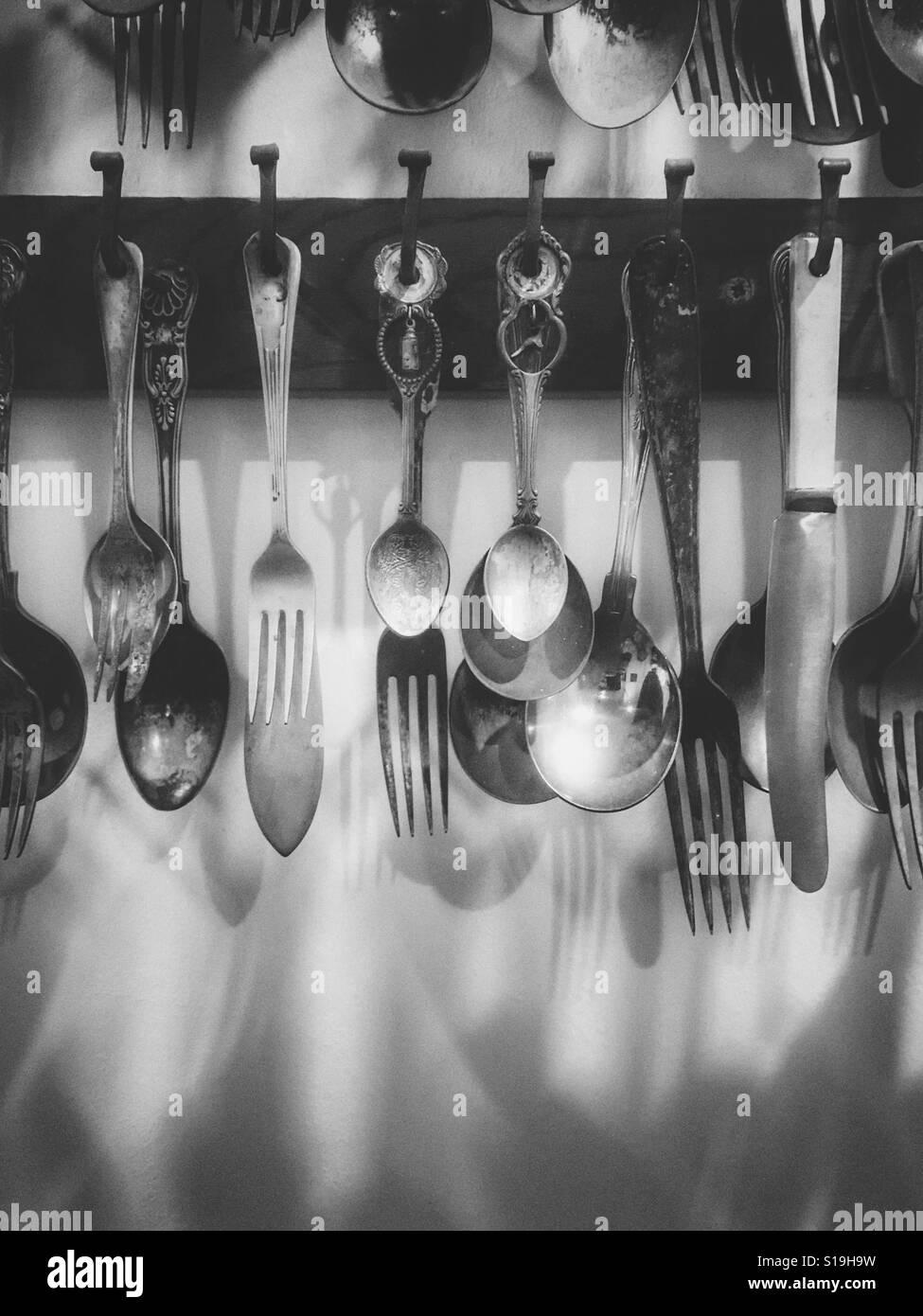 Cuchillos, tenedores y cucharas colgado en una pared. Foto de stock