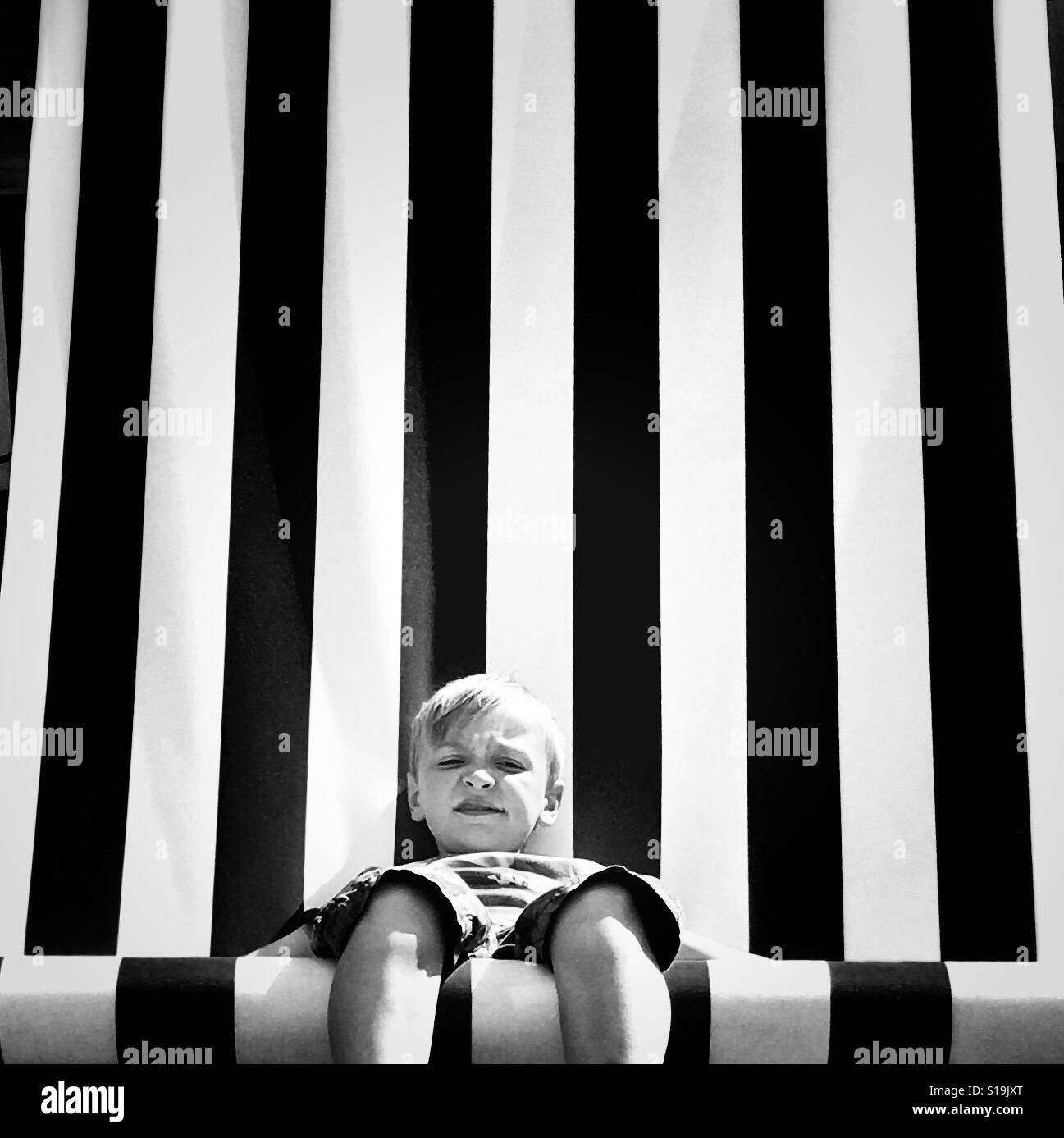 Muchacho sentado en la silla gigante Foto de stock