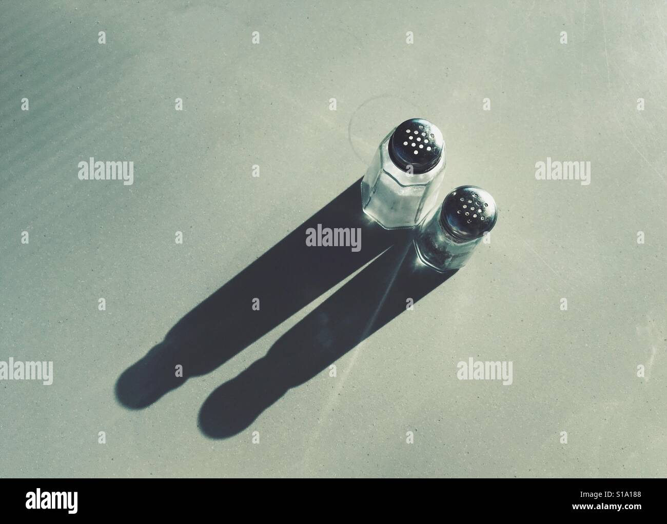 Un alto ángulo de visualización de salero y pimentero que generan largas sombras sobre una mesa Foto de stock