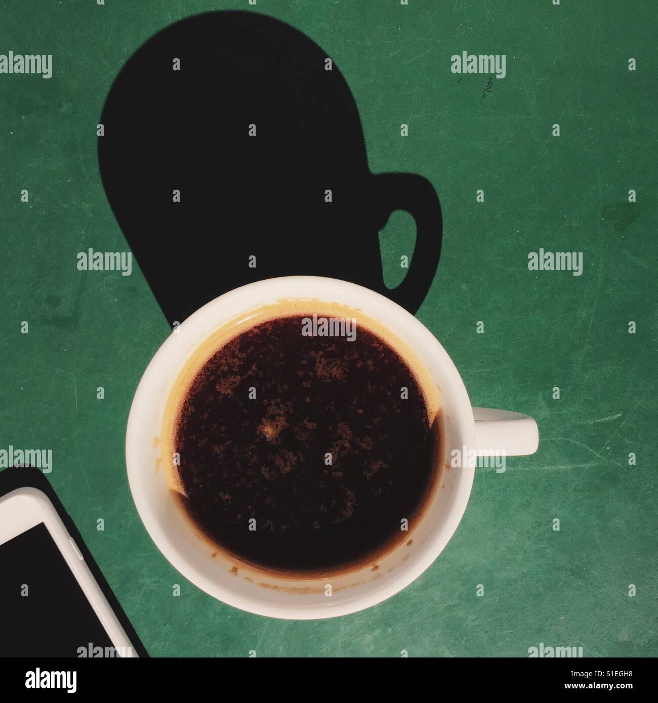 Una fotografía cenital de una fresca bebida de café americano en un cuadro verde con un teléfono Imagen De Stock