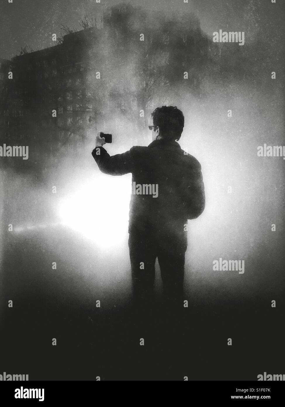 Fotografía en blanco y negro con iluminación dramática de un hombre con su teléfono con cámara en el brazo extendido Foto de stock