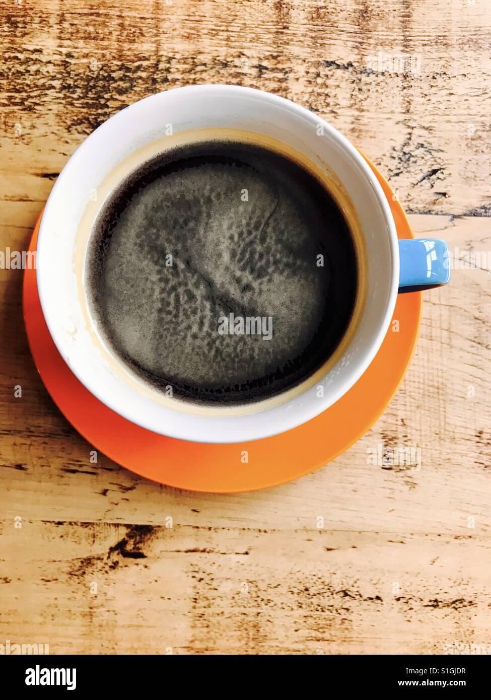 Una taza de café en una mesa de madera Imagen De Stock