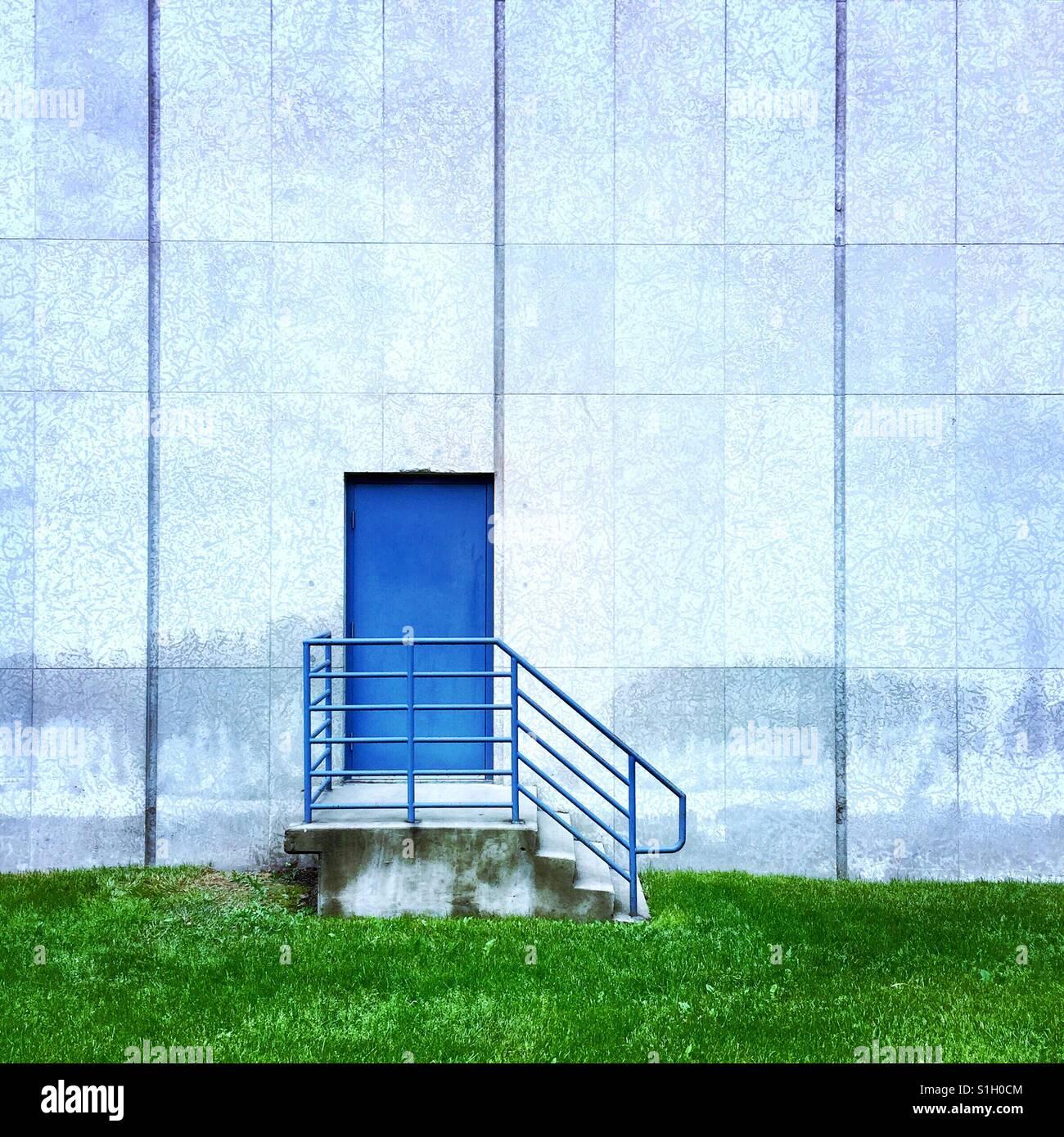 Una simple composición de una puerta azul en el lateral del edificio Imagen De Stock