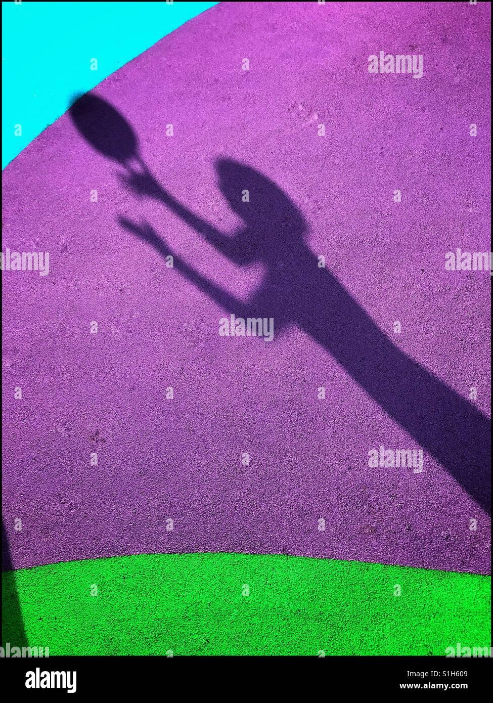 La sombra de un niño que está a punto de agarrar una pelota, es capturada en el fondo de los coloridos Imagen De Stock