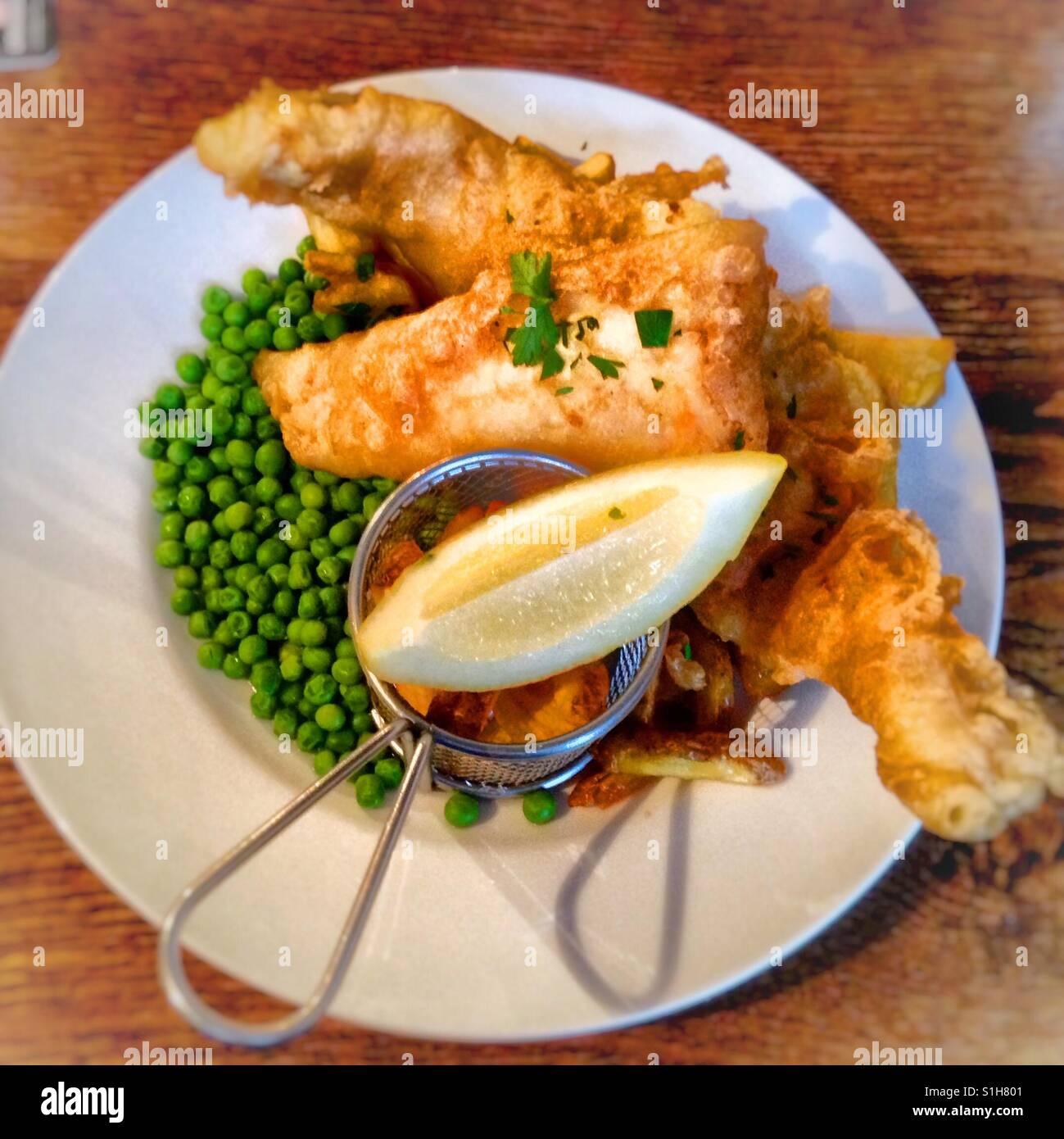 El pescado con patatas fritas y guisantes Imagen De Stock