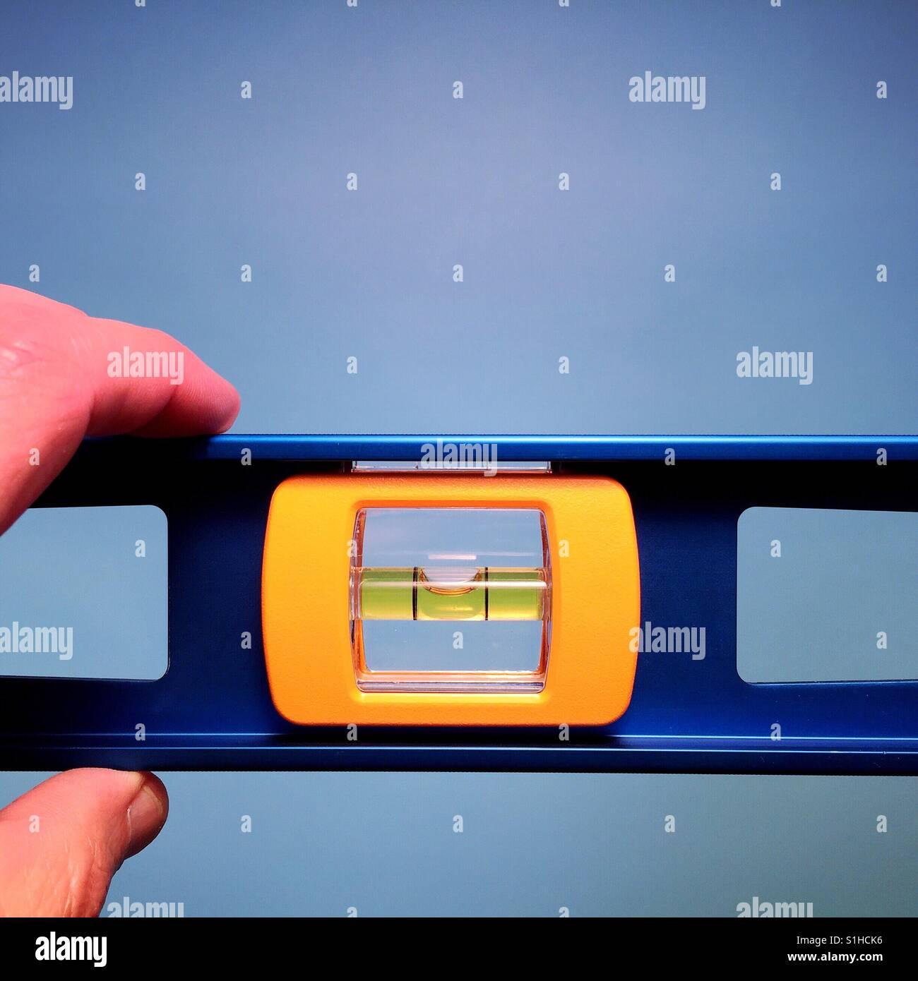 Un primer plano de un hombre sujetando el nivel de un carpintero contra un fondo azul. Imagen De Stock
