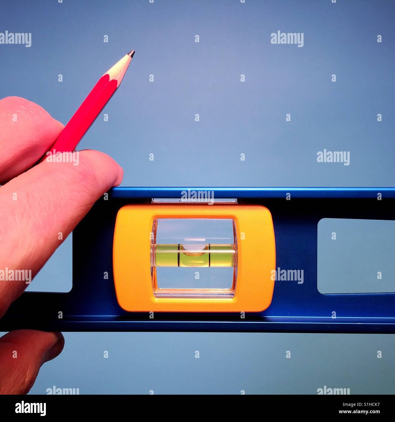 Un primer plano de un hombre sujetando el nivel de un carpintero y un lápiz rojo contra un fondo azul. Imagen De Stock