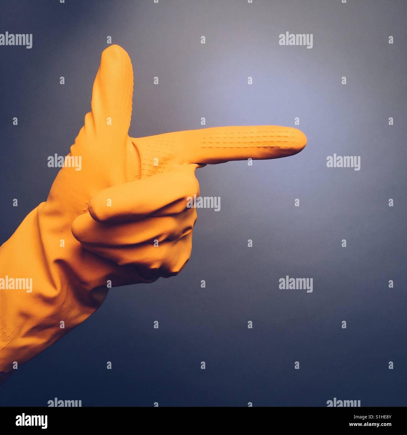 Un hombre de la mano en un guante de goma amarilla haciendo un gesto de mano apuntando contra un fondo azul. Imagen De Stock