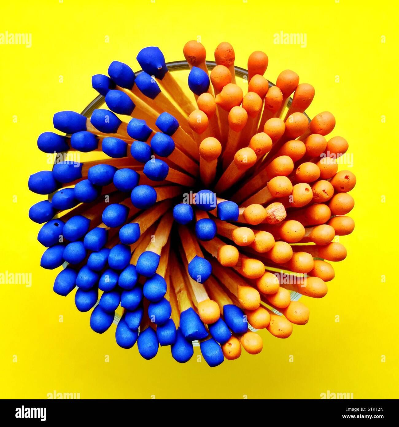 Una fotografía cenital de un montón de cerillas con punta azul y naranja en un recipiente de vidrio Imagen De Stock