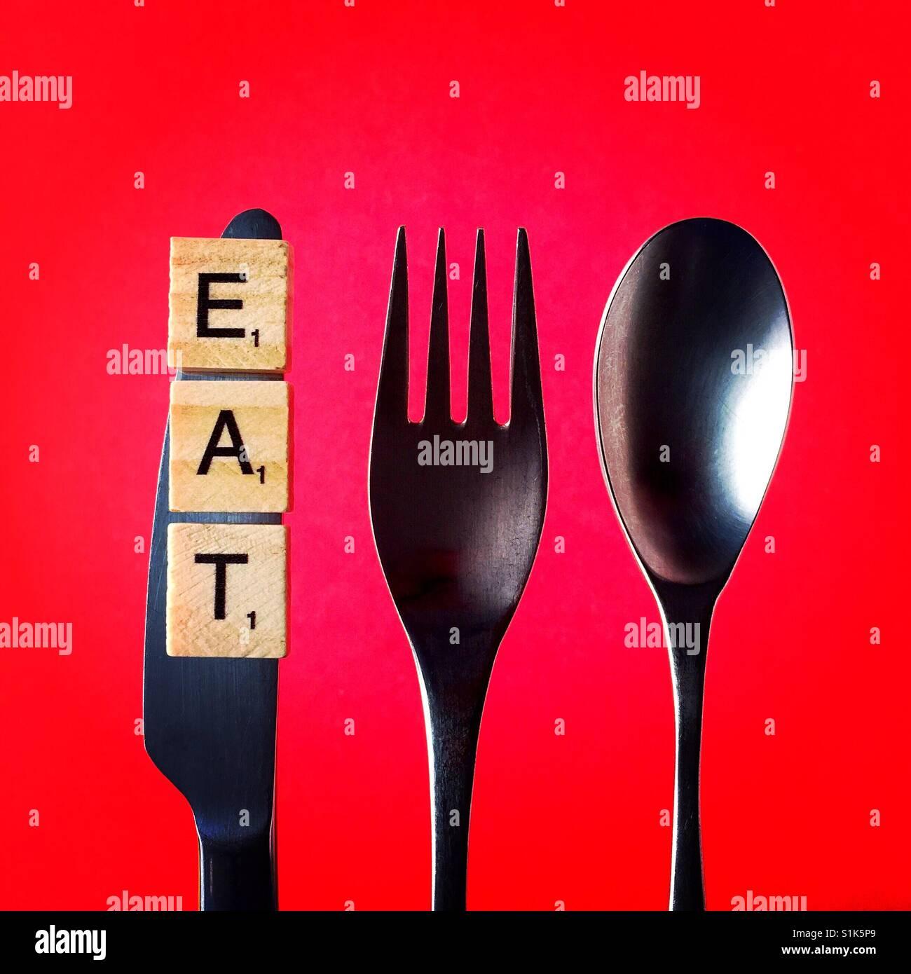 Una fotografía cenital de un cuchillo y un tenedor y una cuchara por encima de un fondo rojo con la palabra Imagen De Stock