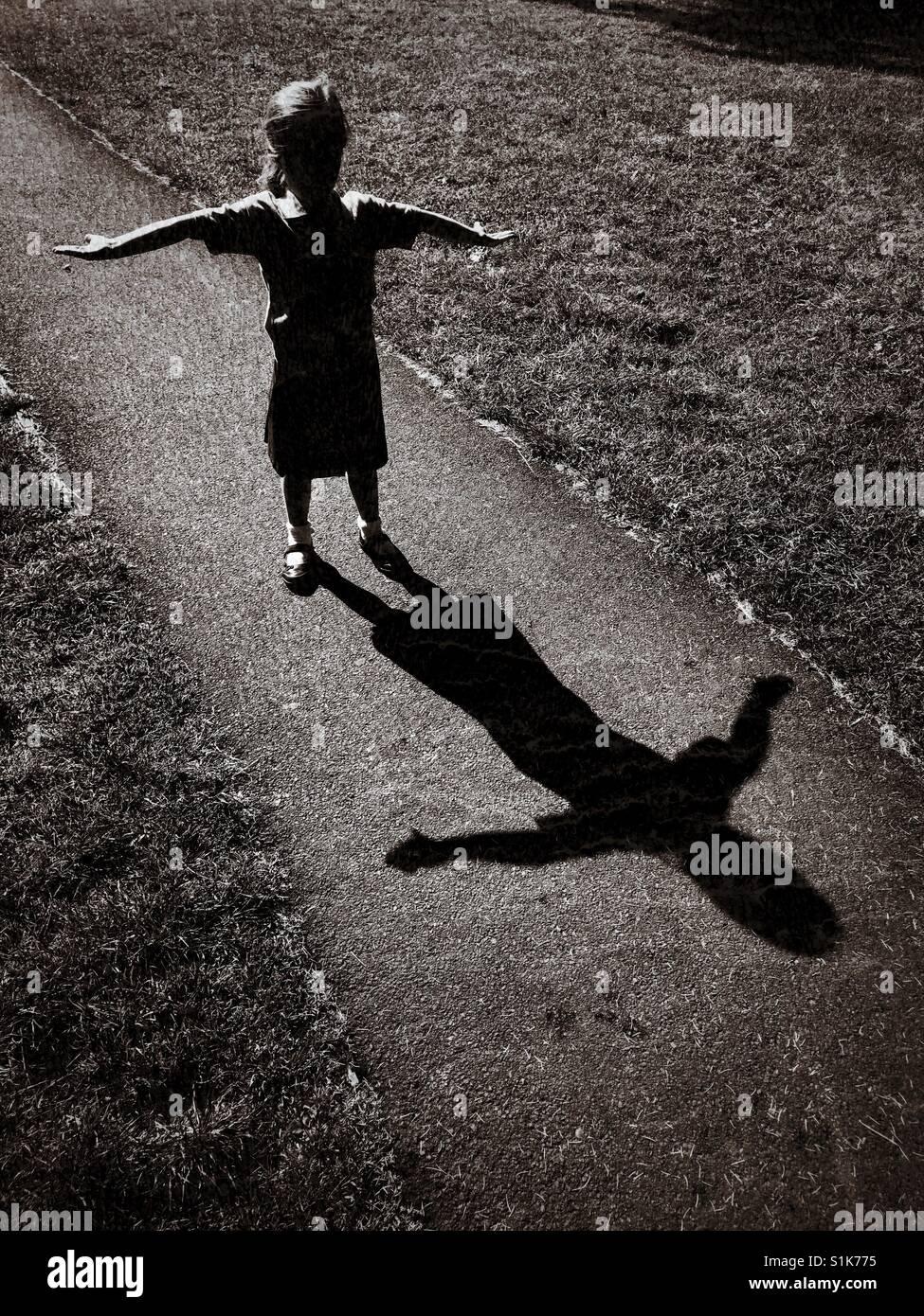 La sombra de un niño de 5 años como ella levanta sus brazos e intenta crear una forma de 't'. Imagen De Stock