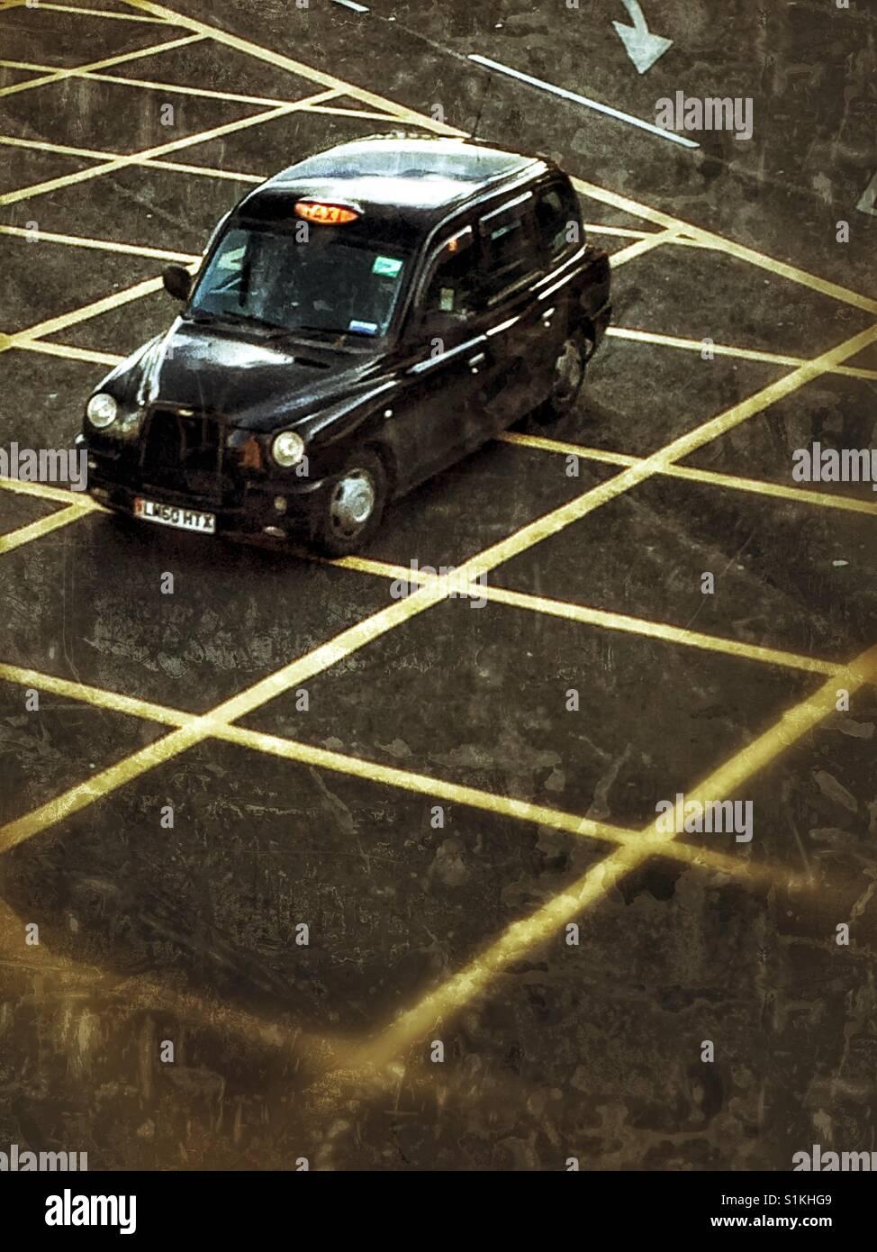 Mirando de arriba abajo en un Black Cab de Londres o taxi amarillo surcando las líneas de emergencia en una calle Foto de stock
