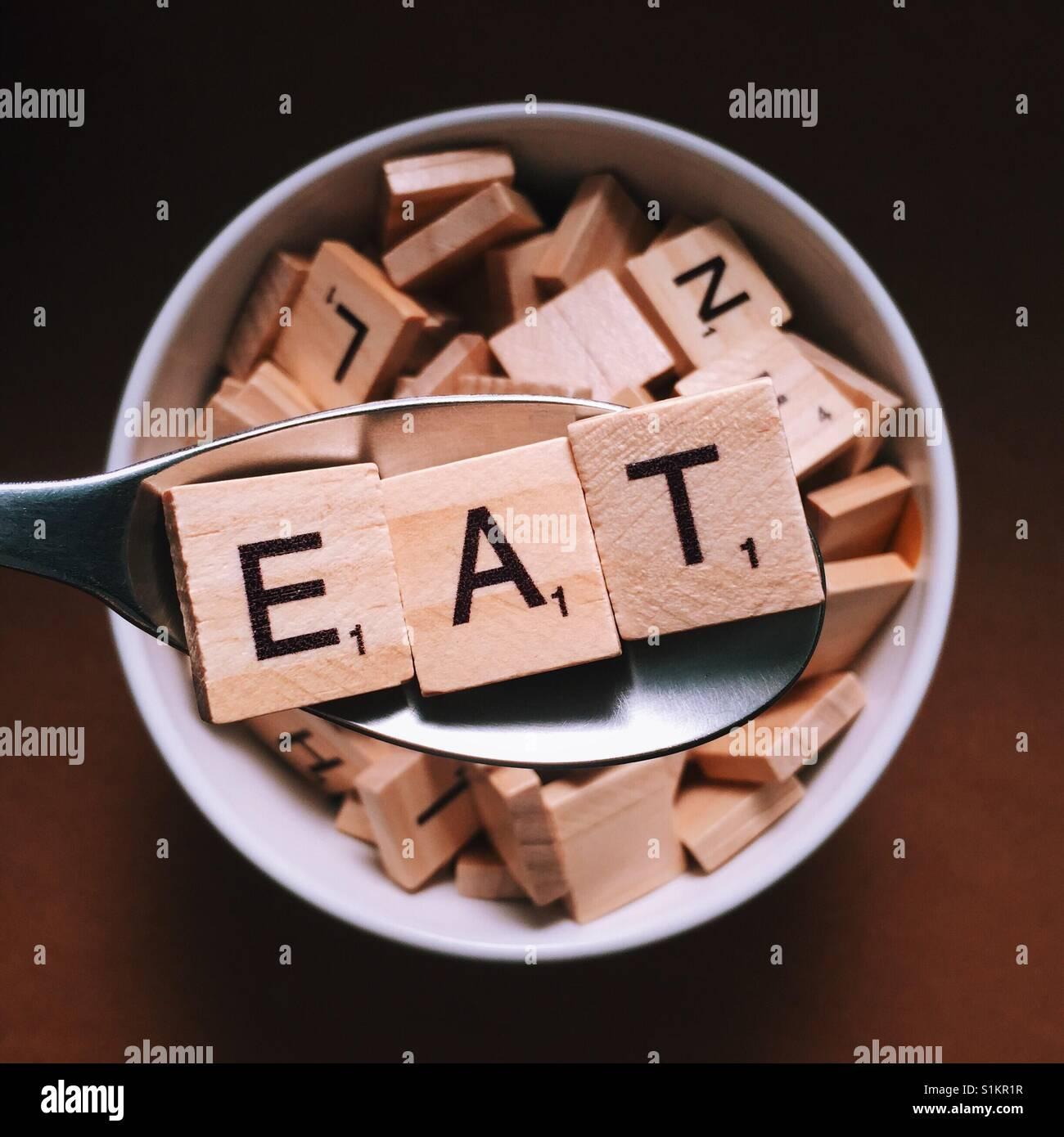 Cerca de una cuchara de madera con letras en ortografía que comer y un cuenco lleno de letras de madera debajo de Foto de stock