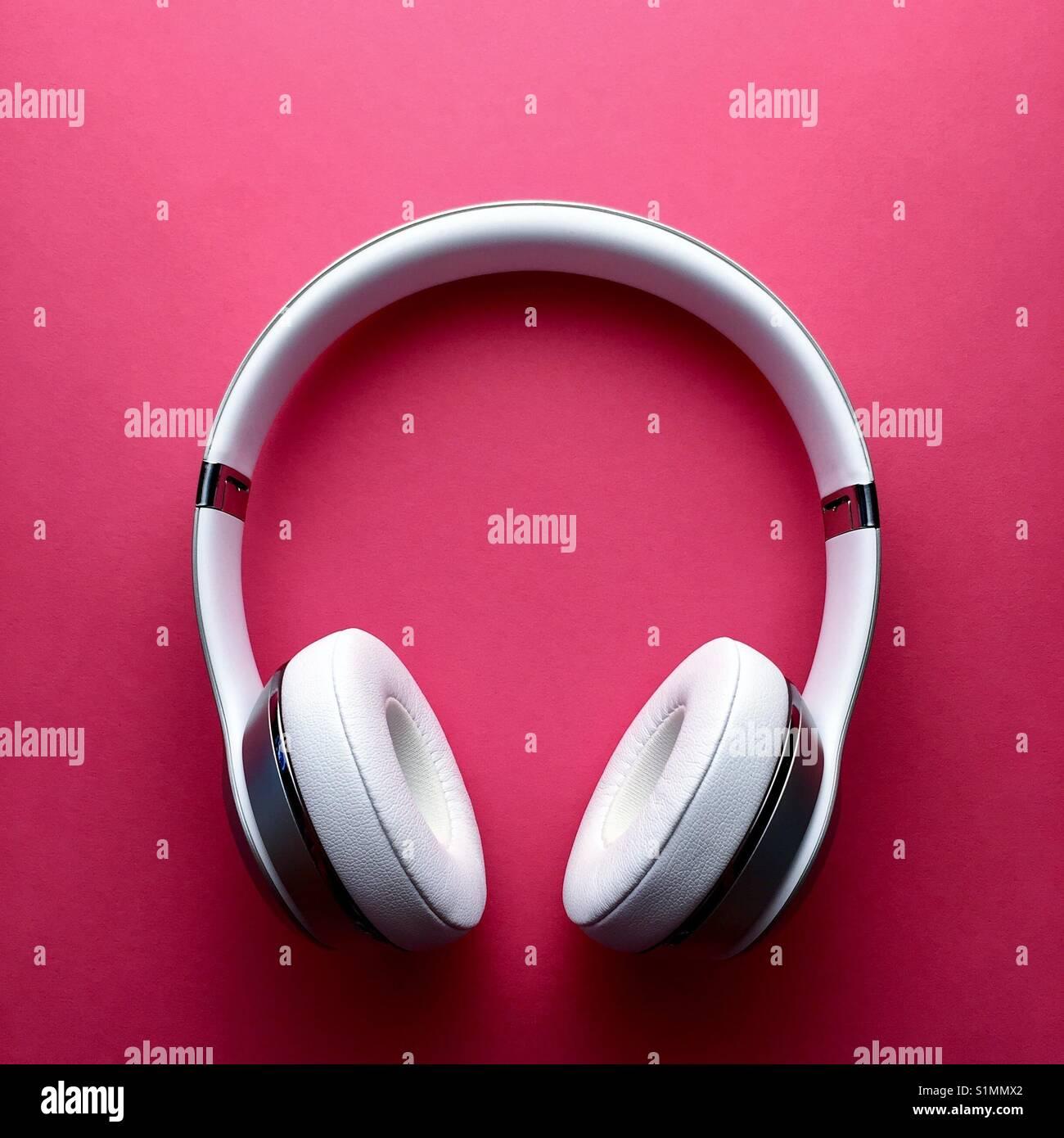 Un conjunto de auriculares inalámbricos blanco sobre un fondo de color rosa rico Imagen De Stock