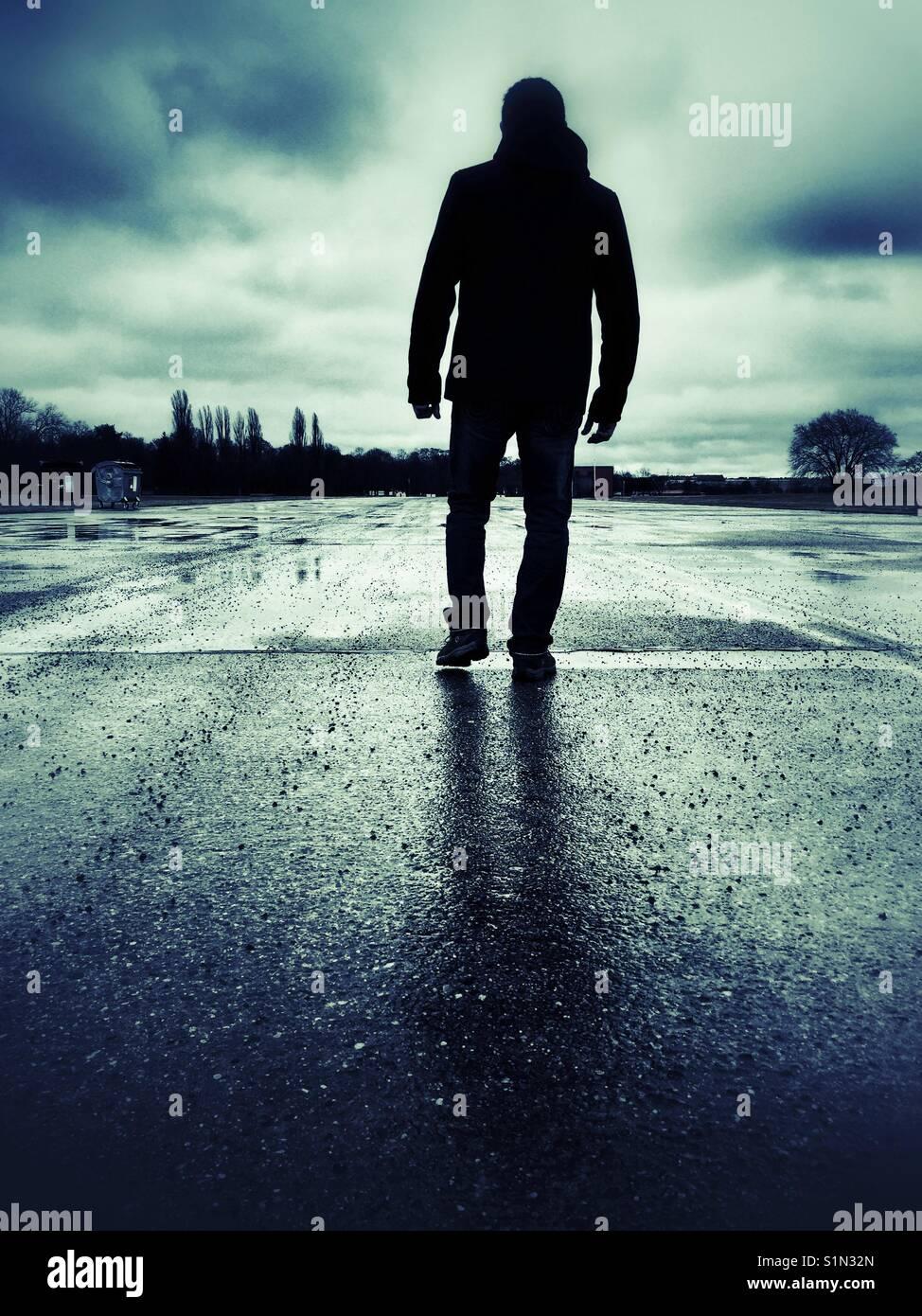 Vista posterior de la silueta de una misteriosa figura masculina caminar al aire libre Imagen De Stock