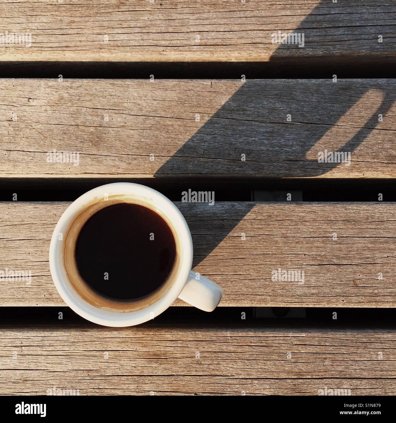 Una sobrecarga simple composición de una fresca bebida espresso americano en un banco de madera con una larga Imagen De Stock